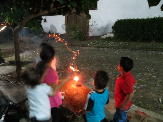 Little kids lighting up little fireworks from a candle